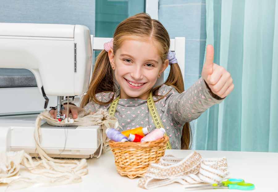 smiling little girl at the table with sewing machine show thumb