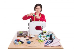 Woman seamstress at the sewing machine. Sewing Accessories.