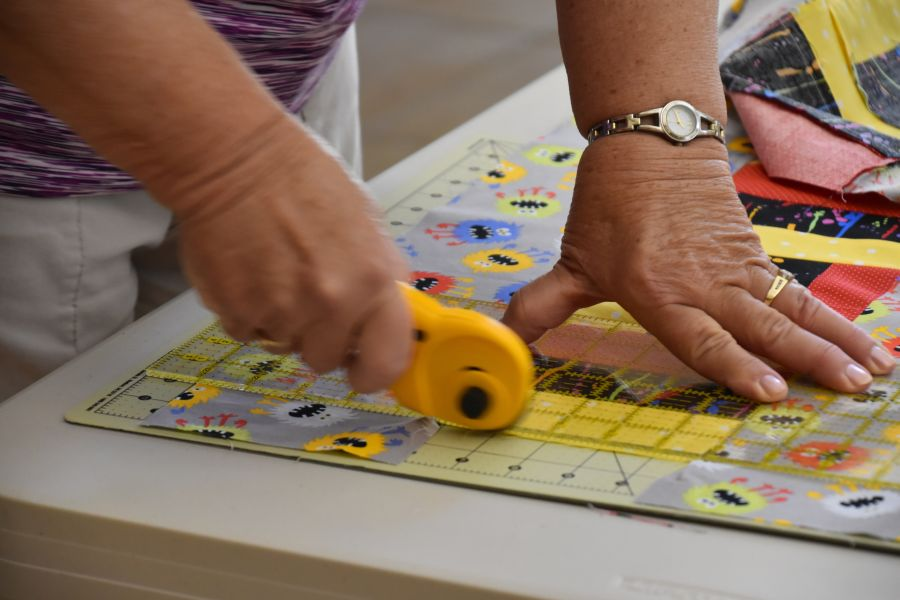 introduction to quilting with woman measuring a block on a quilt